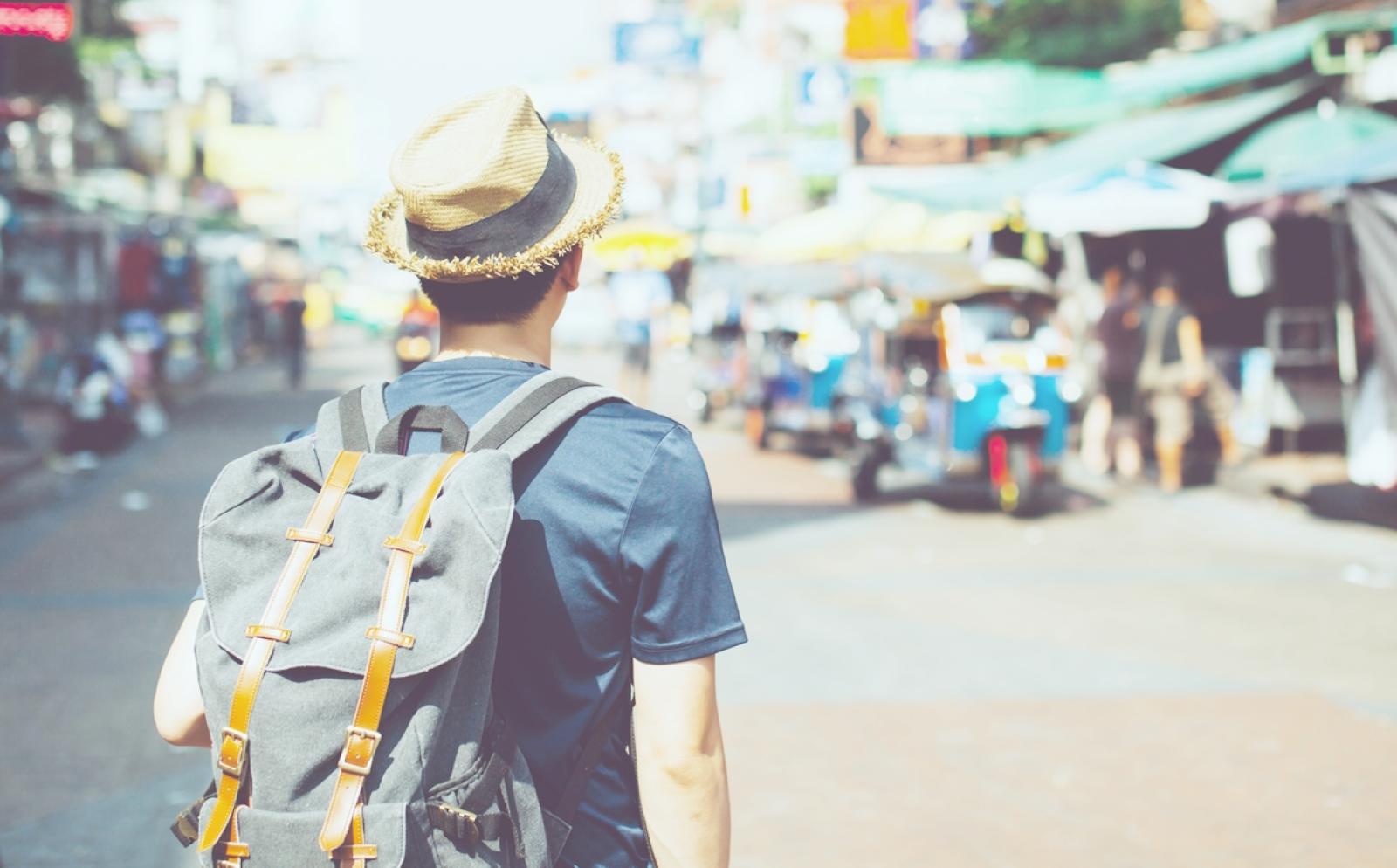 東南アジアの繁華街を探検する学生ボランティアの後ろ姿